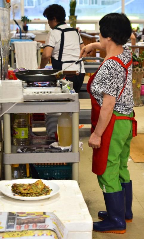 Korean woman cooking food for Erik